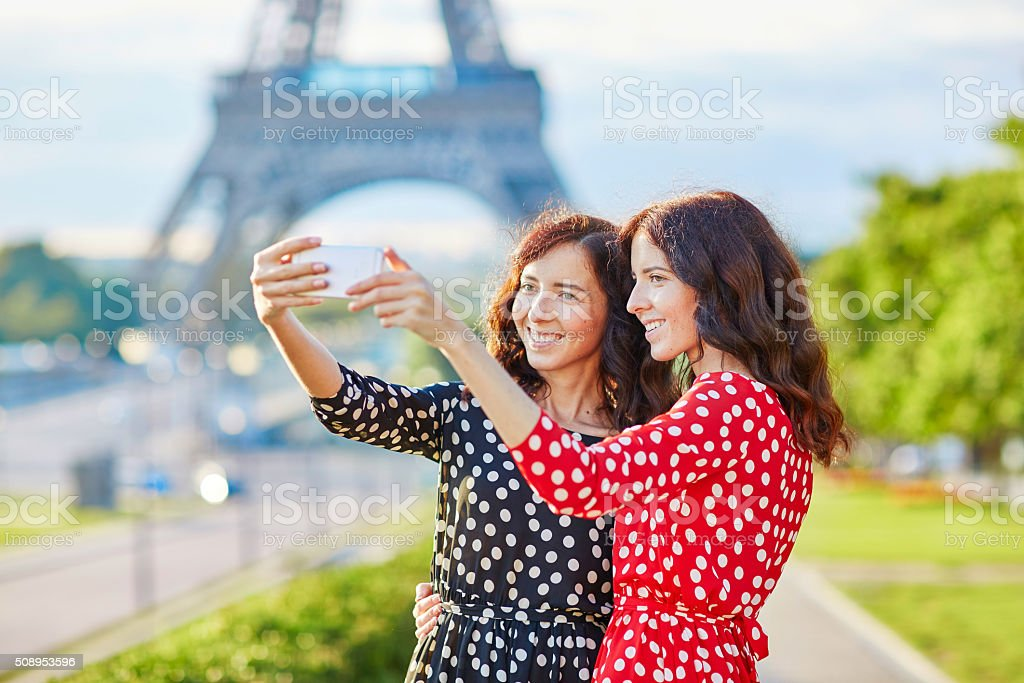 Beautiful twin sisters taking selfie in front of Eiffel Tower stock photo