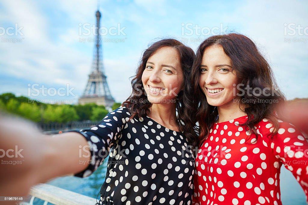 Beautiful twin sisters taking selfie stock photo