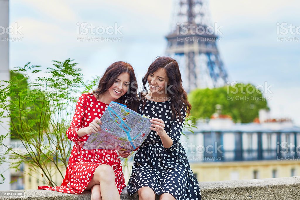 Beautiful twin sisters using map in front of Eiffel Tower stock photo