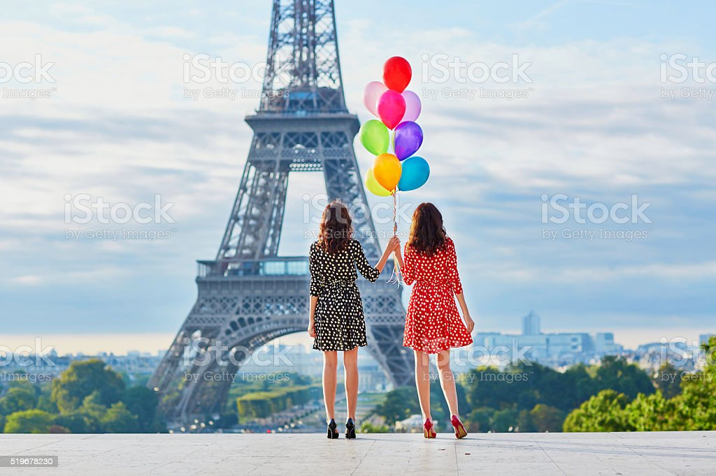 Beautiful twin sisters with colorful balloons stock photo