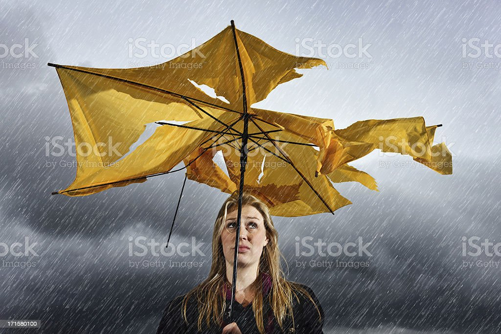Beautiful unhappy blonde with ruined umbrella getting soaked in thunderstorm stock photo