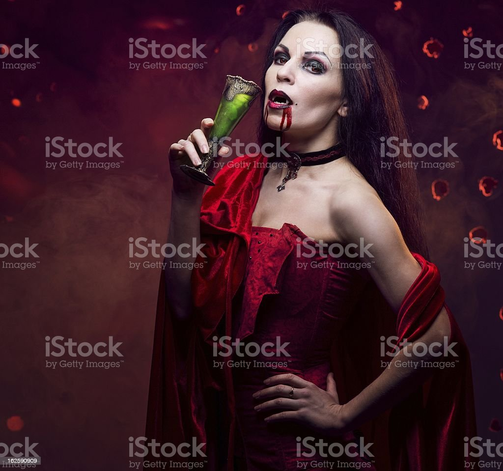 Beautiful vampire woman in red dress drinking royalty-free stock photo