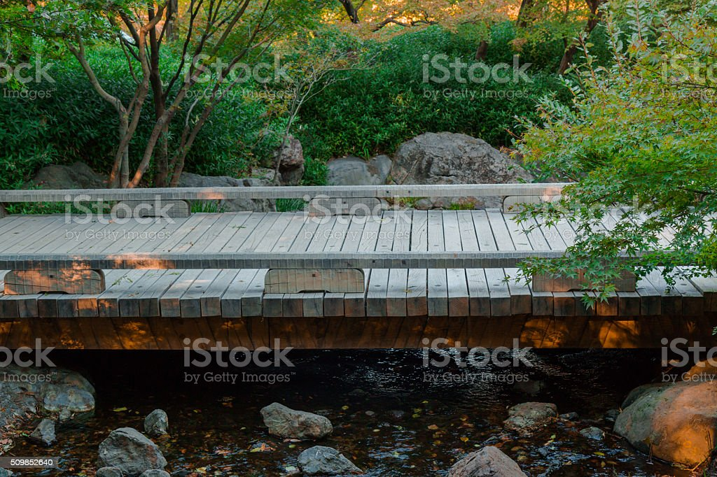 Beautiful view of a small wooden bridge over a river. stock photo