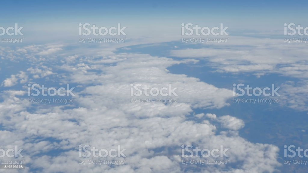 Beautiful view of the blue sky with clouds from the porthole of the plane during the flight stock photo