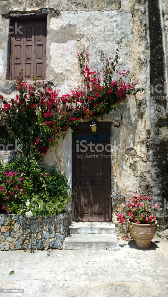 Beautiful view of the building with entrance door and blooming flowers around her. Vertical view stock photo