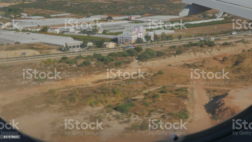 Beautiful view of the land from the porthole. The plane lands on the ground. stock photo