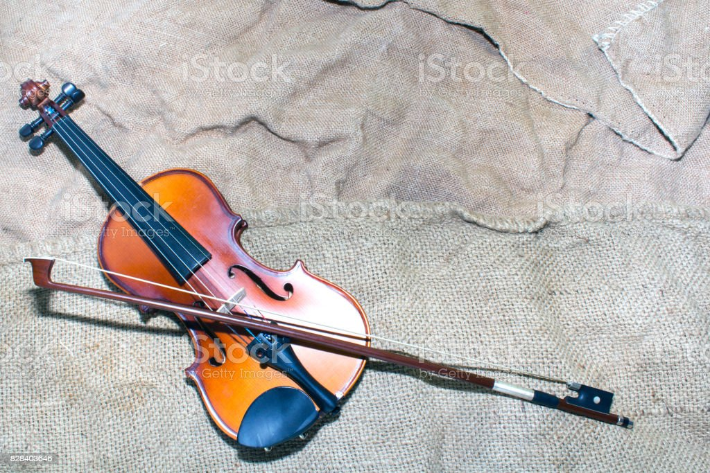 beautiful violin rests on an old piece of material. stock photo