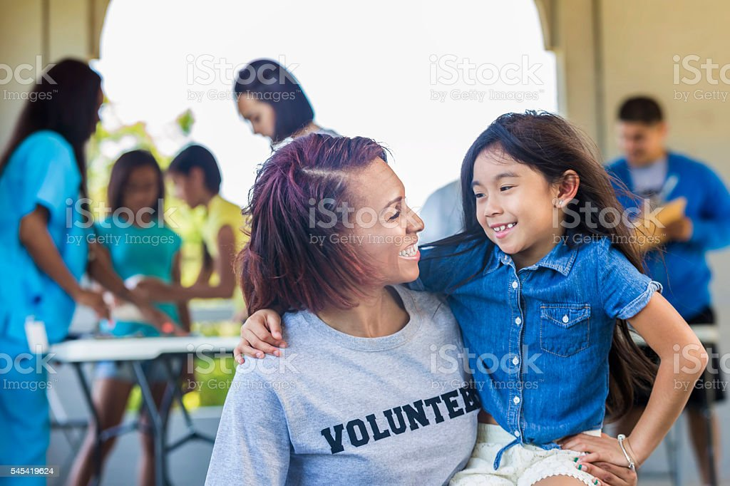 Beautiful volunteer and adorable little girl smile at each other stock photo