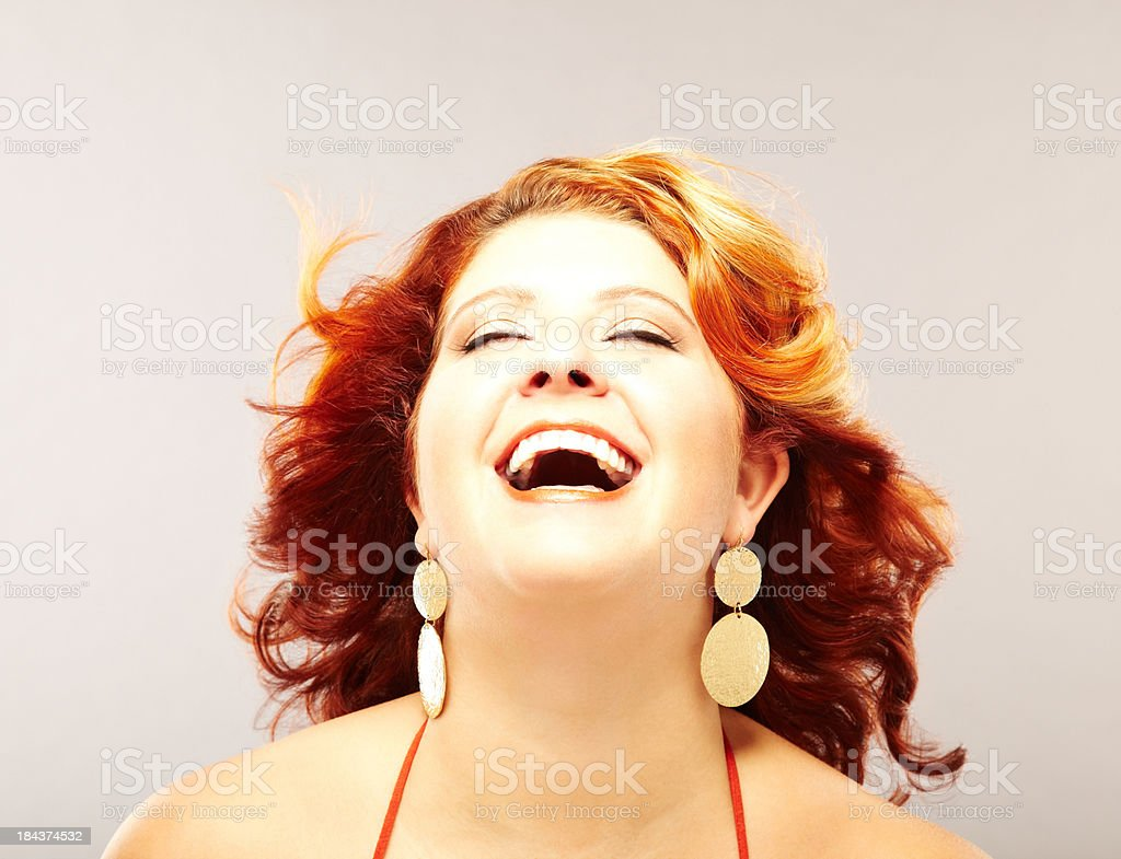 Beautiful voluptuous redhead fashion model laughing looking up stock photo