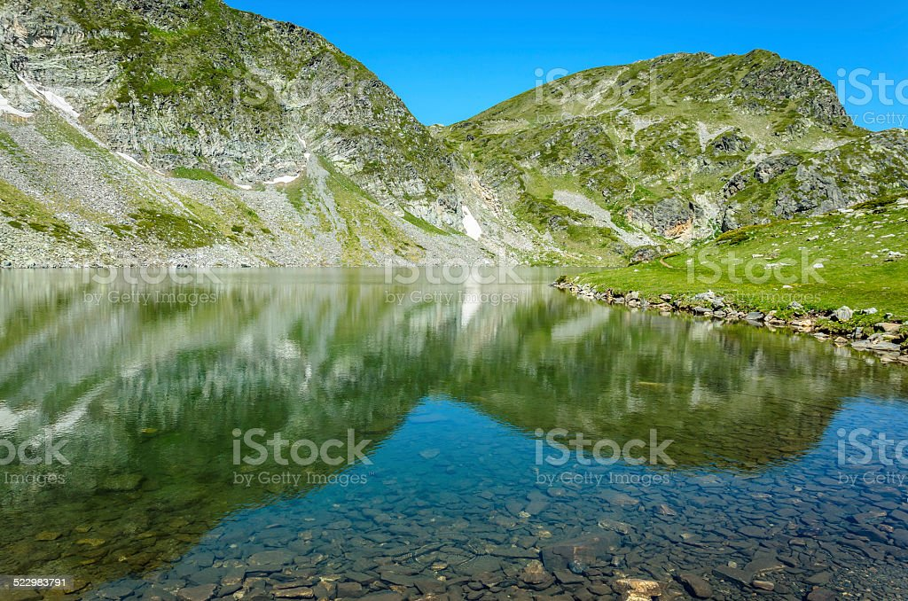 Hermosa agua con reflejos del lago de montaña de foto de stock libre de derechos