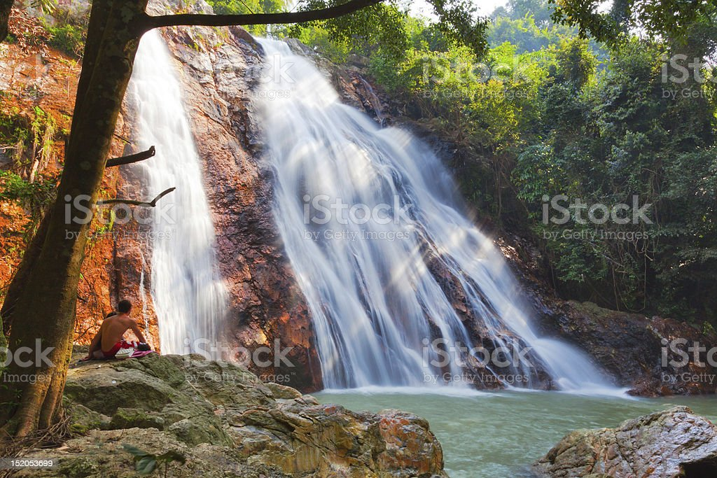 Beautiful waterfalls in the woods falling into a lake stock photo
