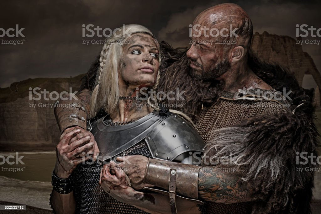Beautiful weapon wielding viking warrior couple in emotional pose stock photo