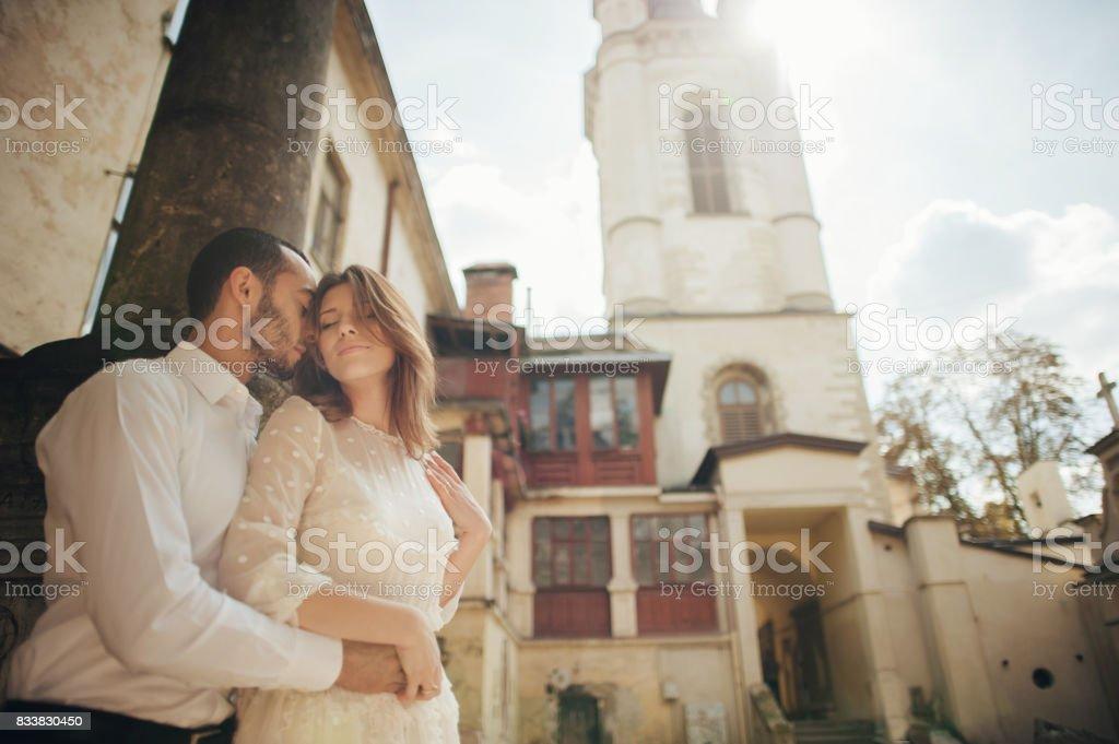 beautiful wedding couple hugging standing near old building stock photo