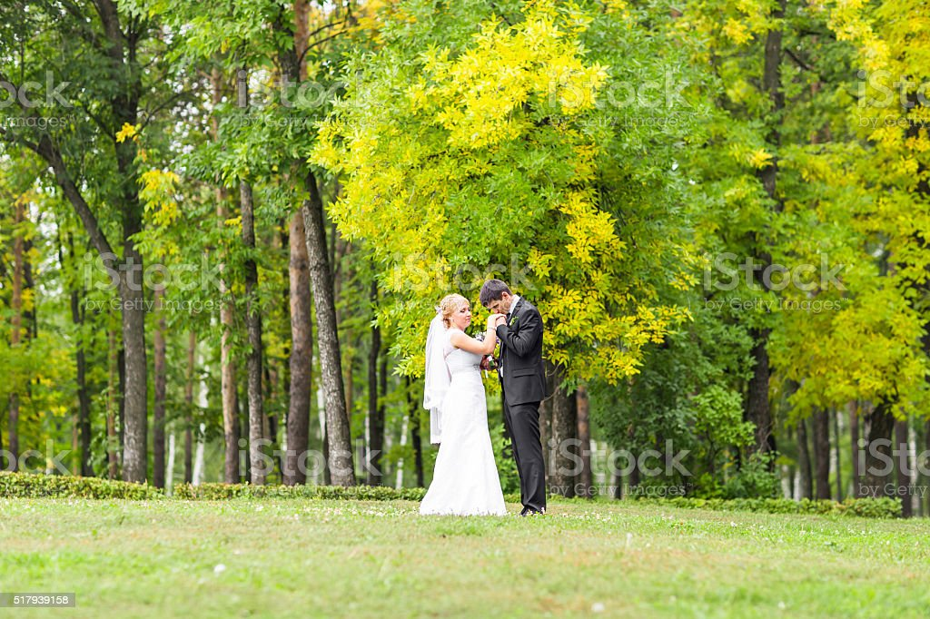 Beautiful wedding couple in park. They kiss and hug each stock photo