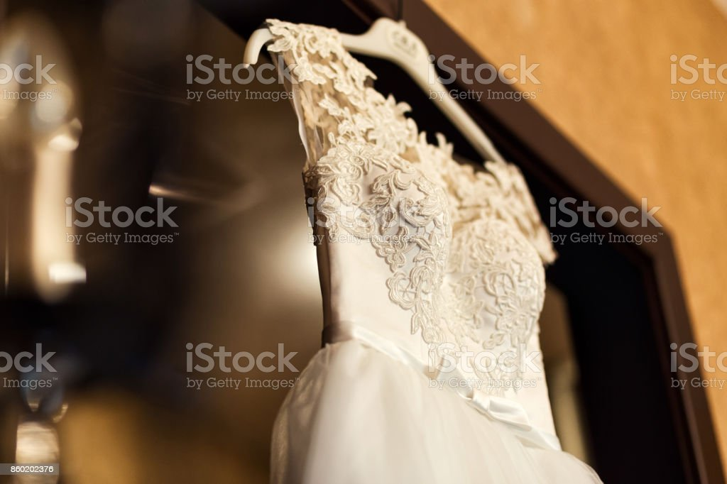 beautiful wedding dress hanging in the room, bridal accessories,...