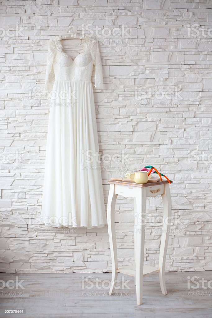 Beautiful wedding dress on hanger white brick wall stock photo