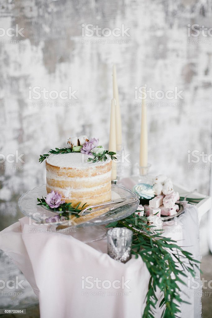 Beautiful wedding round cake with floral decorations and candles. stock photo
