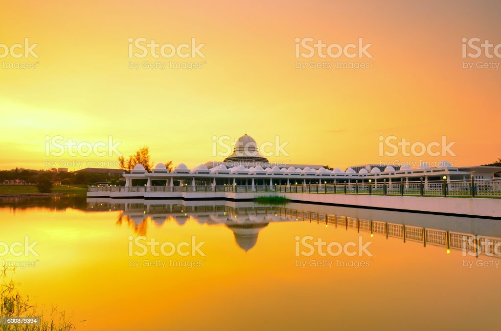Beautiful white mosque during burning sunrise with mirror reflec stock photo
