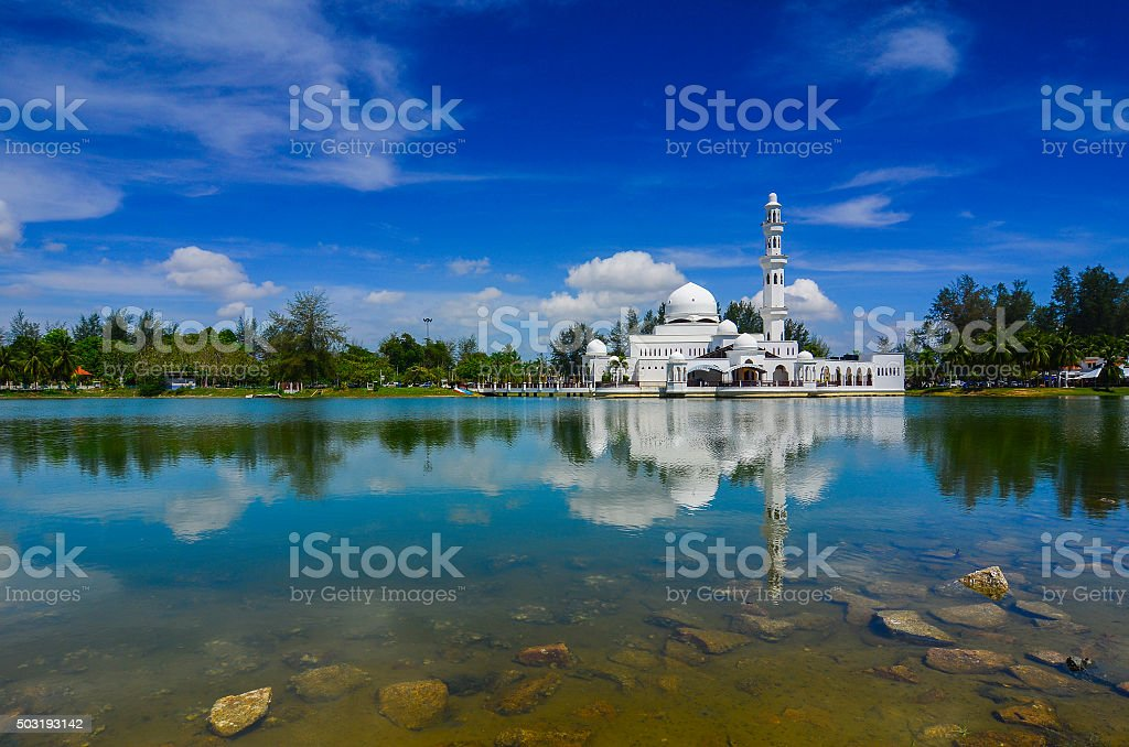 Beautiful white mosque with reflection in the lake during clean stock photo