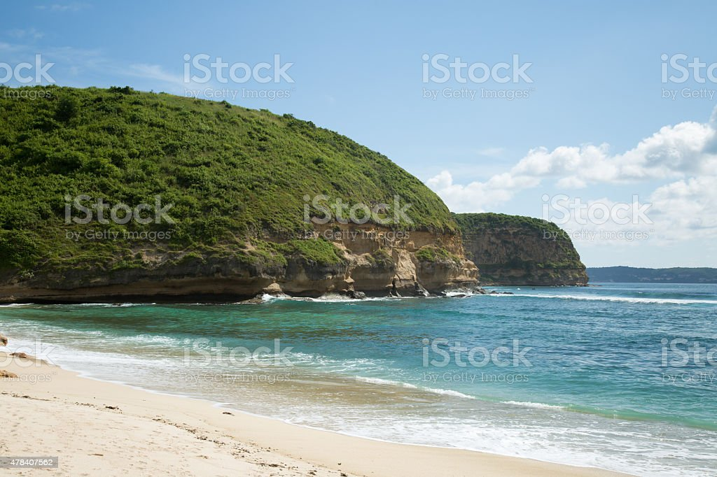 Beautiful white sand beach and blue ocean with green mountain. stock photo