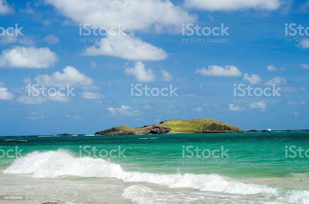 beautiful white sand beach waves and distant island stock photo
