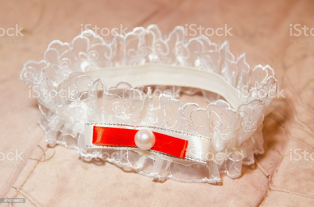Beautiful white wedding garter with red stripe stock photo