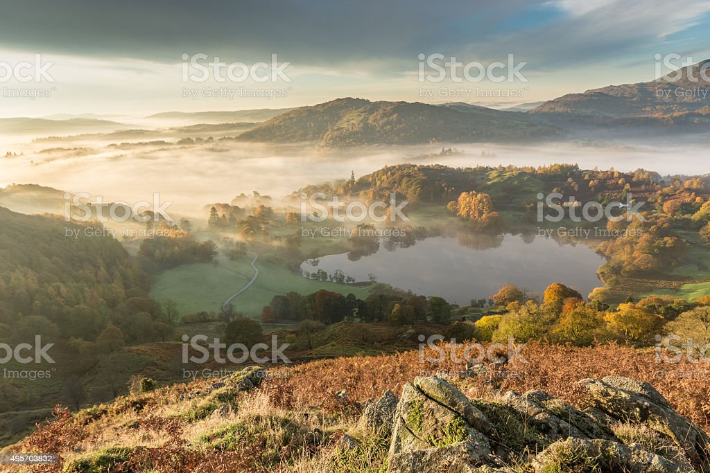 Beautiful Wide Angle View Of Morning Fog Over Langdale Valley. stock photo