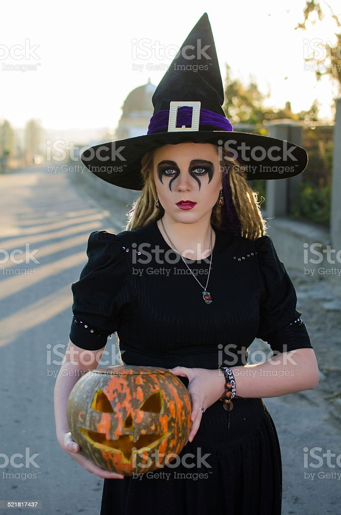 Beautiful witch with a pumpkin on Halloween stock photo