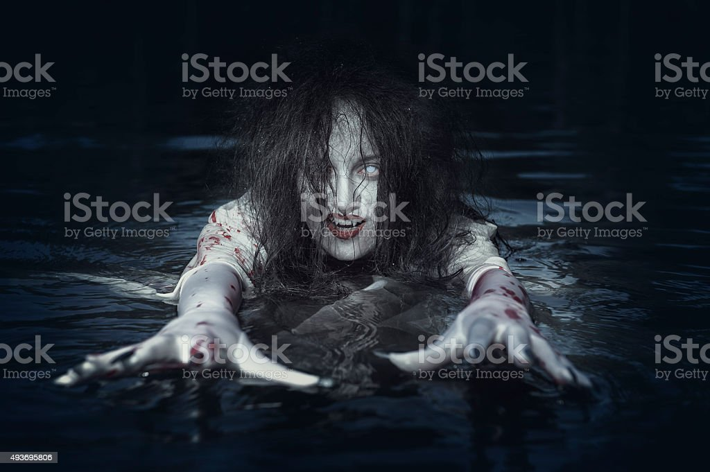 Beautiful witch woman standing in the river stock photo