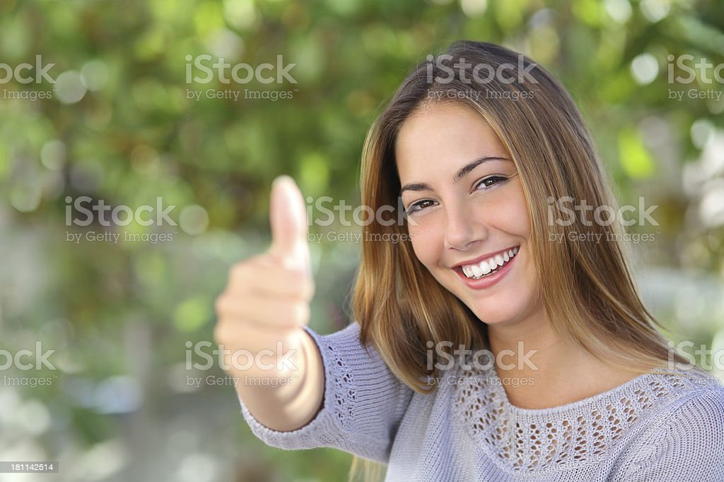 Beautiful woman agreement with thumb up outdoor stock photo