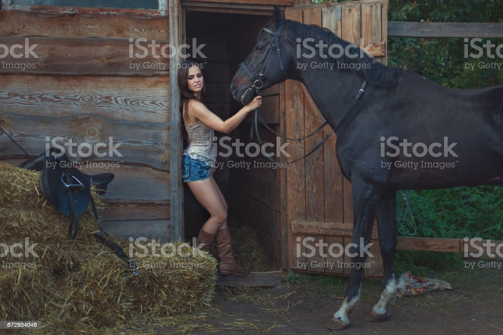 Beautiful woman and a horse on a farm. stock photo
