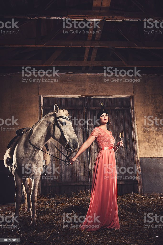 Beautiful woman and horse in riding house stock photo