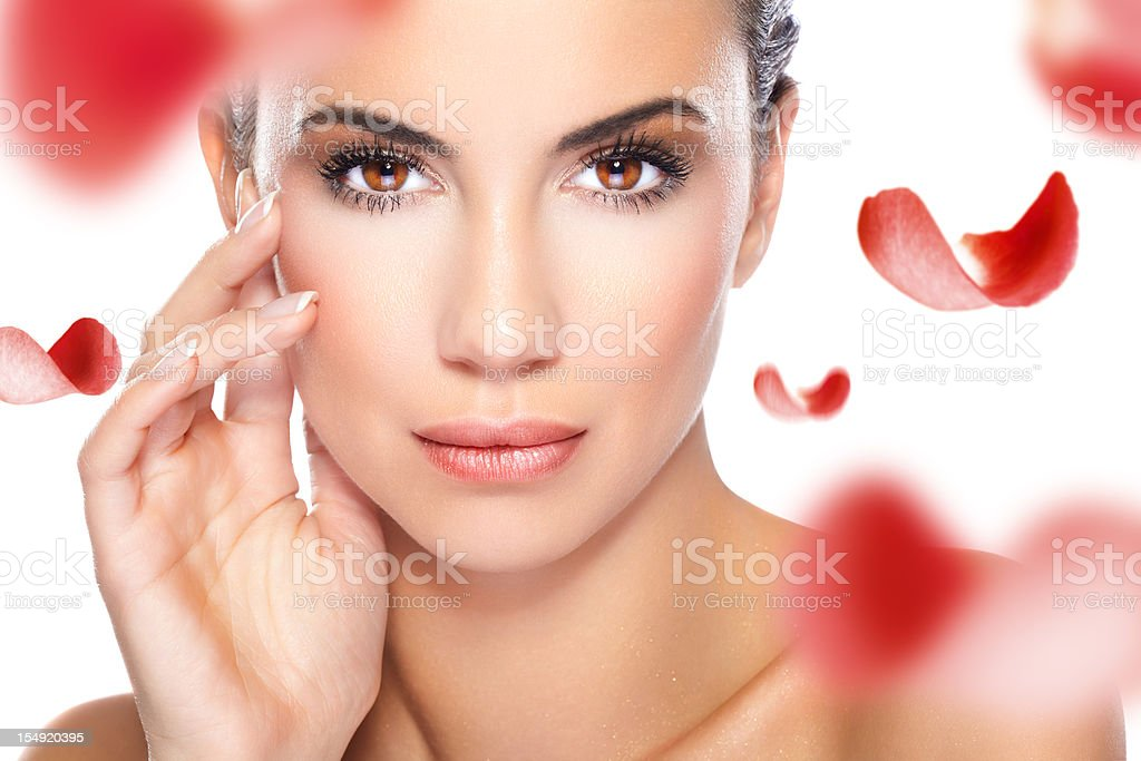 Beautiful woman and red rose petals stock photo