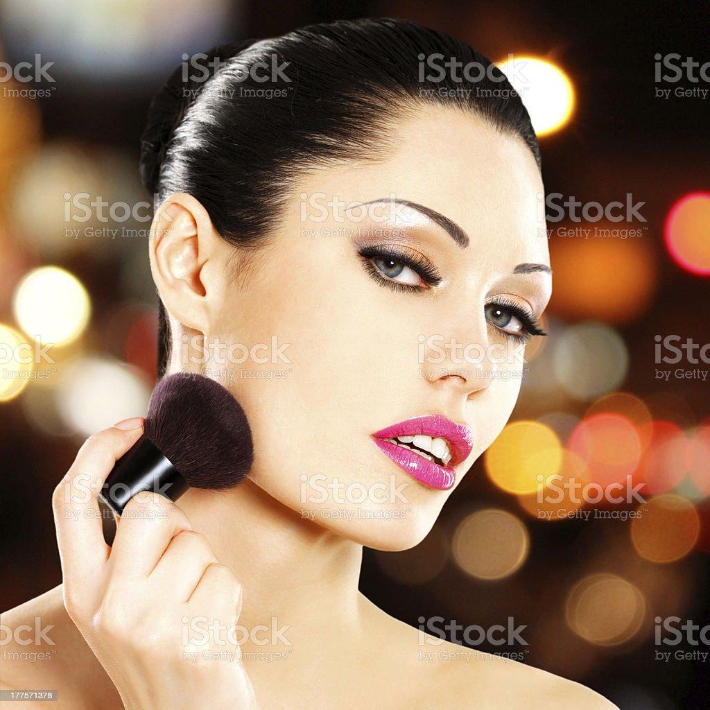 Beautiful woman applying blusher on face royalty-free stock photo