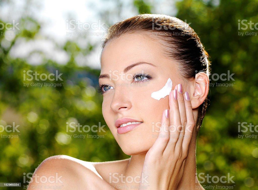 Beautiful woman applying cream on cheek royalty-free stock photo