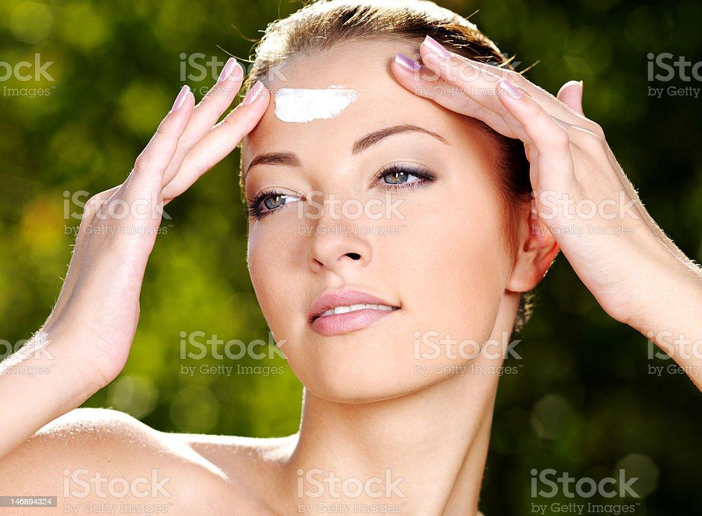 Beautiful woman applying cream on forehead stock photo