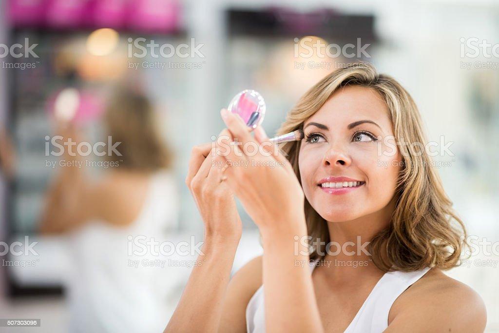 Beautiful woman applying makeup stock photo