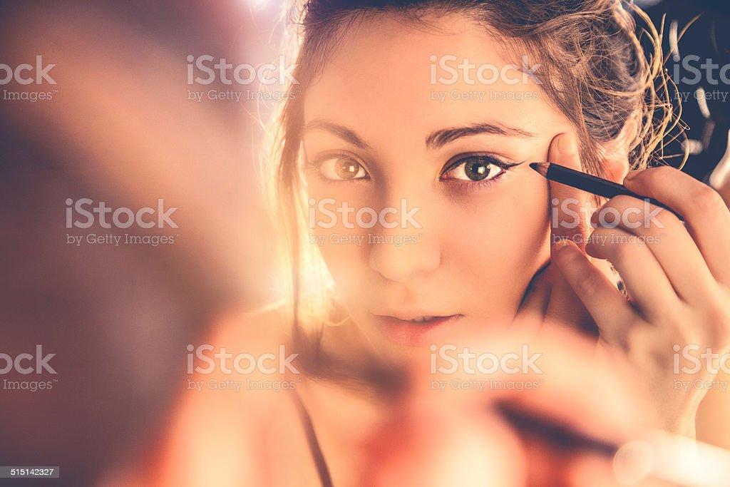 Beautiful woman applying make-up stock photo