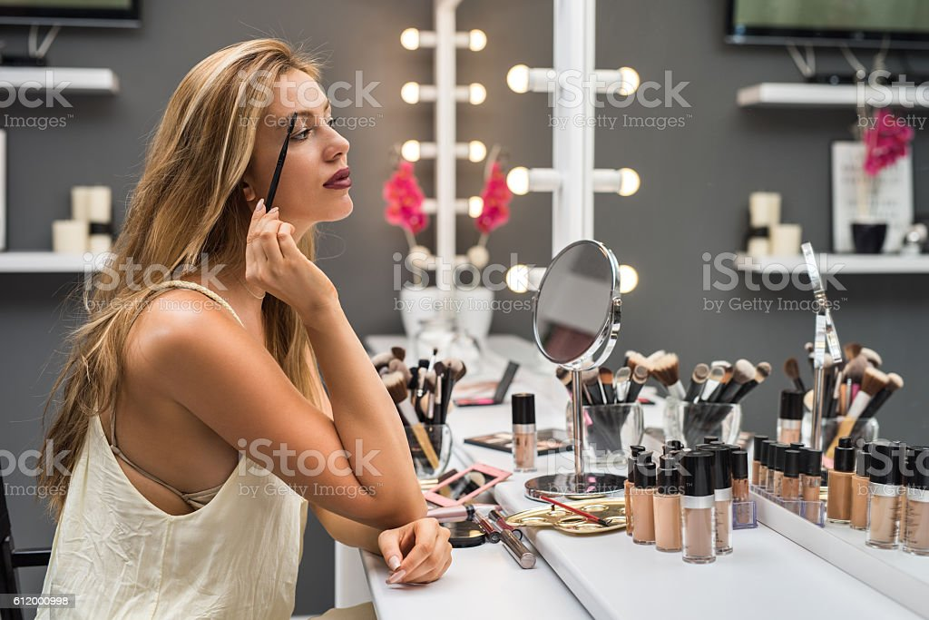 Beautiful woman applying mascara on her eyelashes in beauty salon. stock photo
