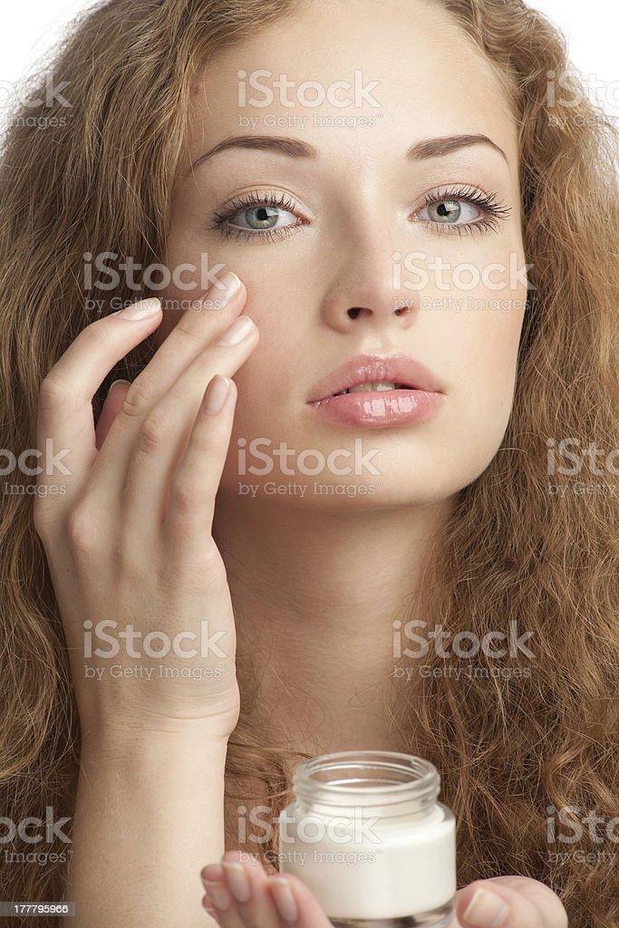 Beautiful woman applying moisturizing cream royalty-free stock photo