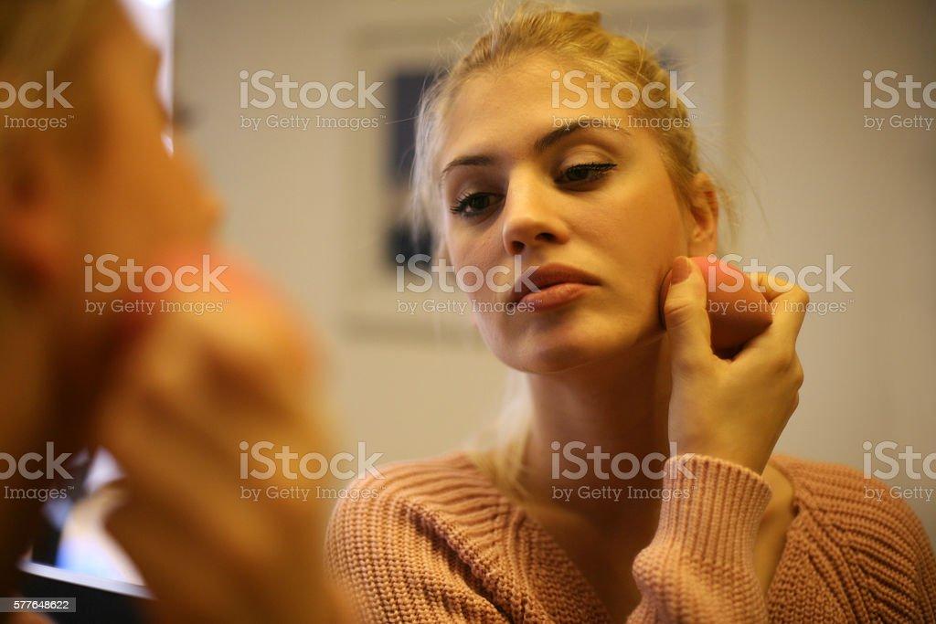 Beautiful woman applying powder on her face. stock photo