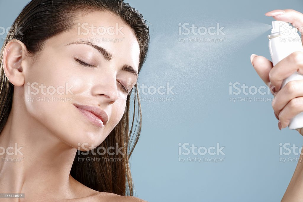 Beautiful woman applying spray  water treatment on face stock photo