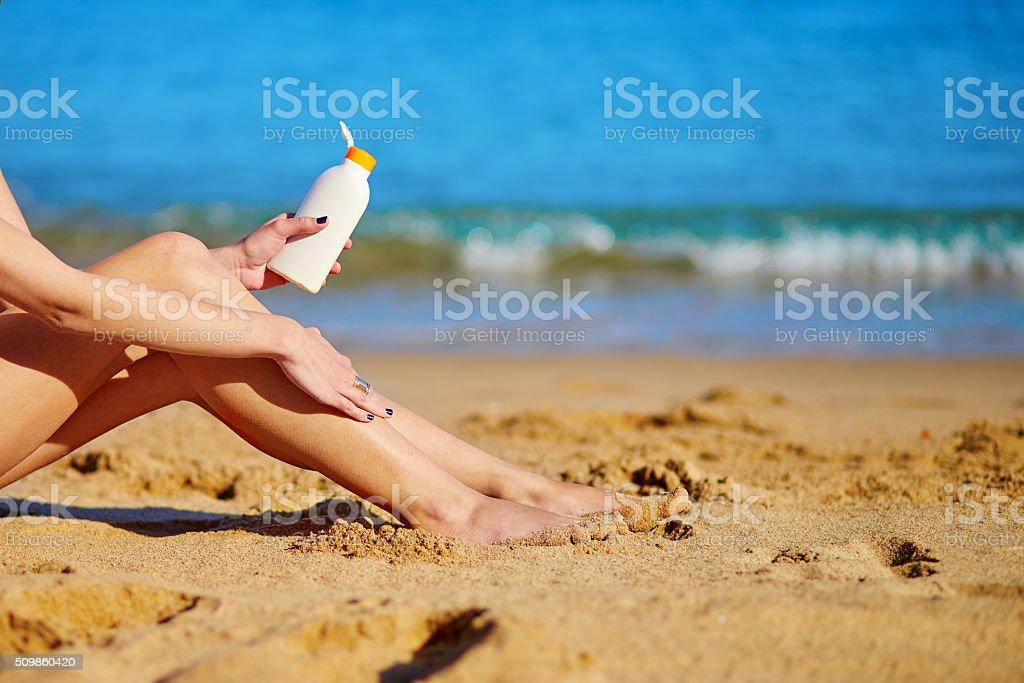 Beautiful woman applying sunscreen on her legs stock photo