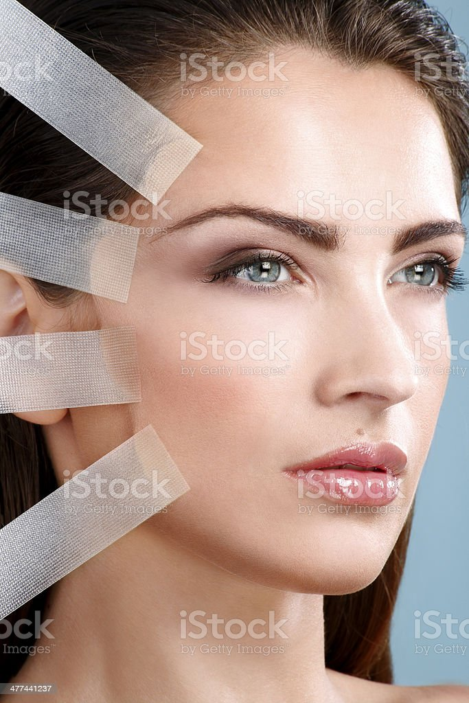Beautiful woman applying tape lifting treatment on face stock photo