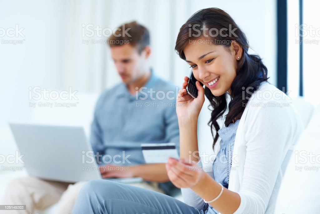 Beautiful woman at home paying bills with credit card royalty-free stock photo