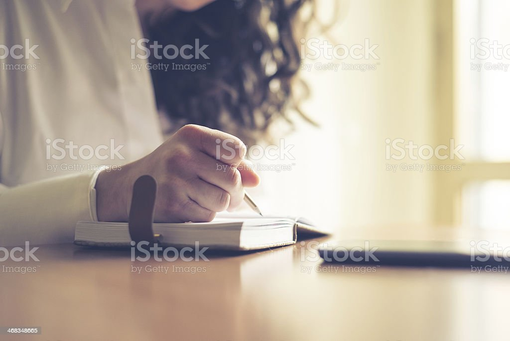 beautiful woman at home writing and working stock photo