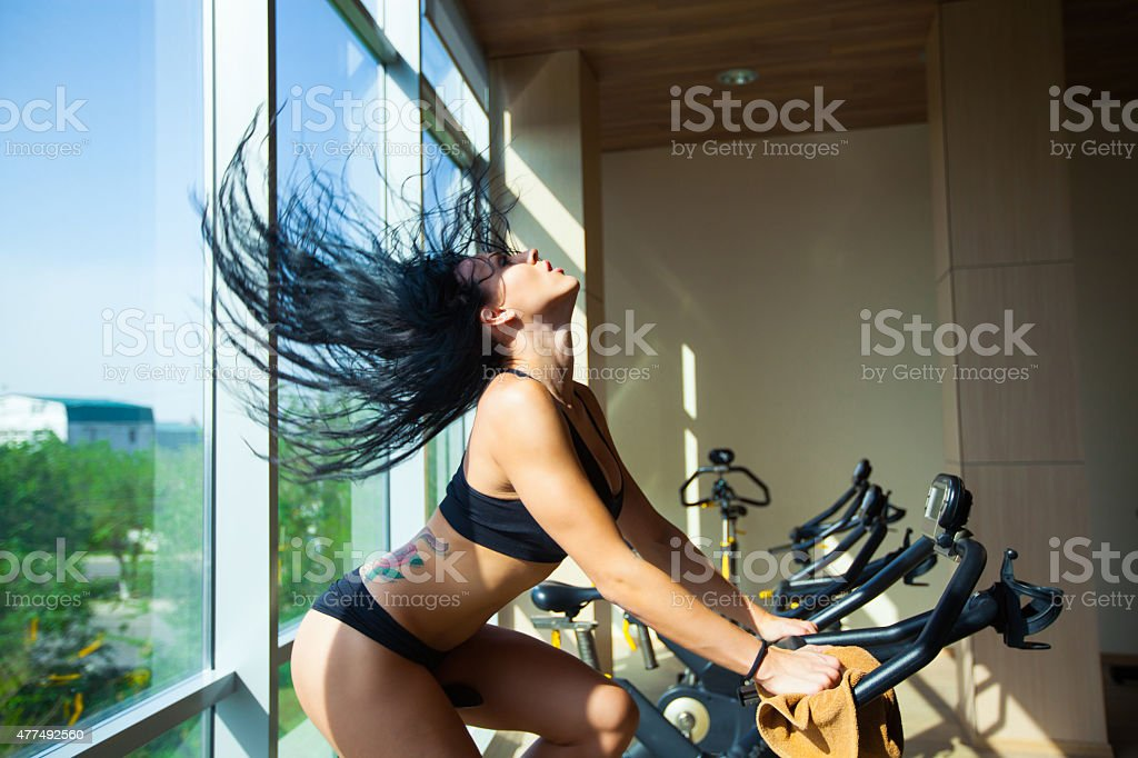 Beautiful woman at the gym on bike, cycle, hair stock photo