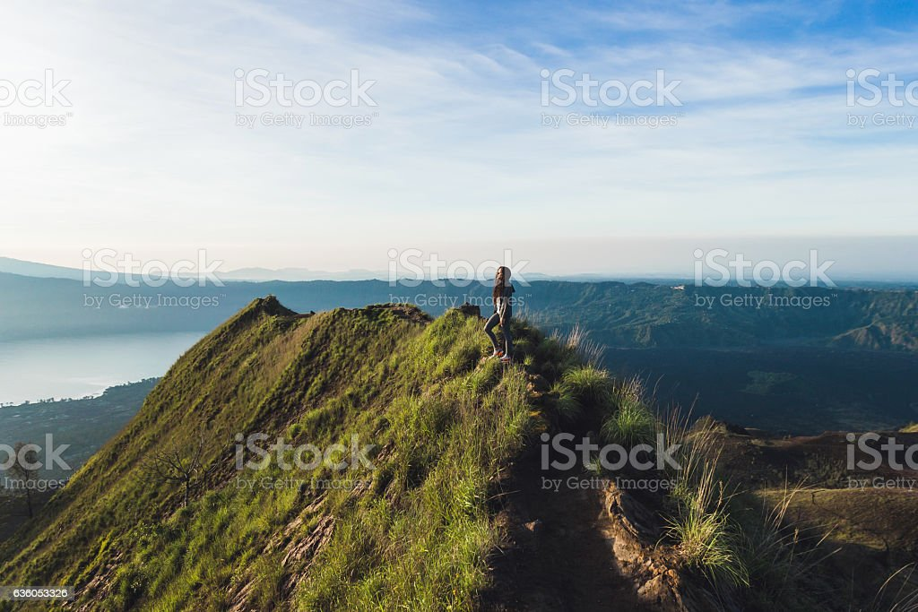 Beautiful woman at the top of Mount Batur, Bali, Indonesia stock photo