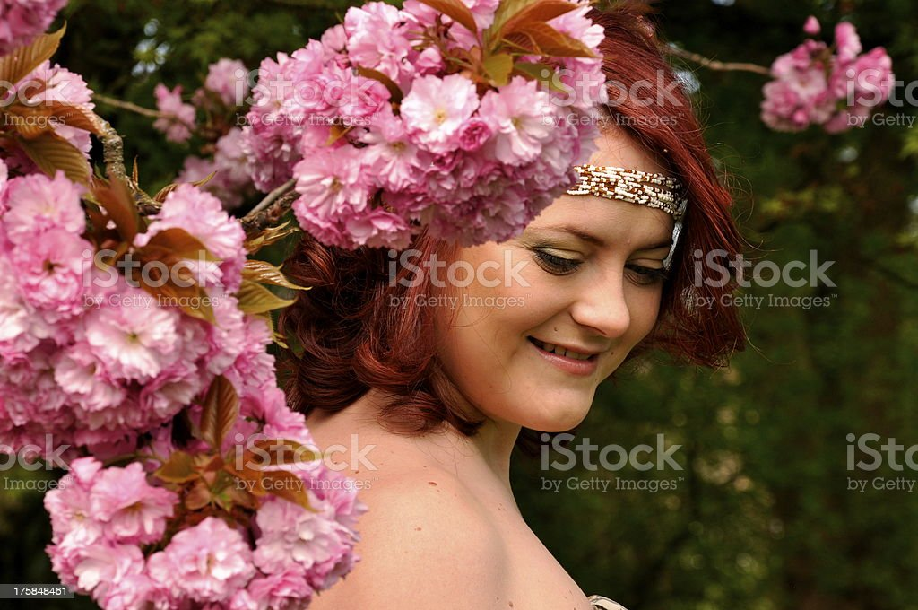 Beatiful woman behind blooming sakura stock photo