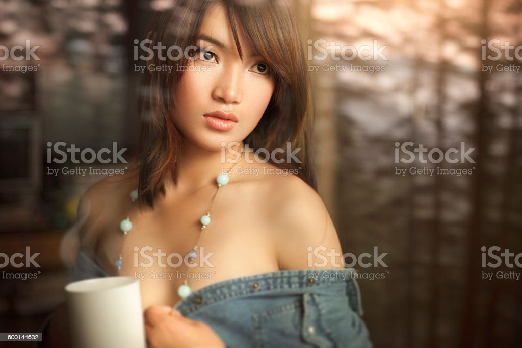 Beautiful woman behind glass window at home with coffee mug. stock photo